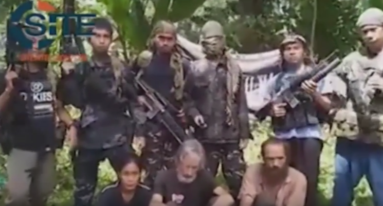 A video circulating in the Internet shows Canadian Robert Hall, girlfriend Marites Flor, and Norwegian Kjartan Sekkingstad, flanked by masked ASG members, begging the Canadian and Philippine governments to comply with the bandits demand. (Screengrab of ASG's new video obtained by SITE, an extremist monitoring organization)