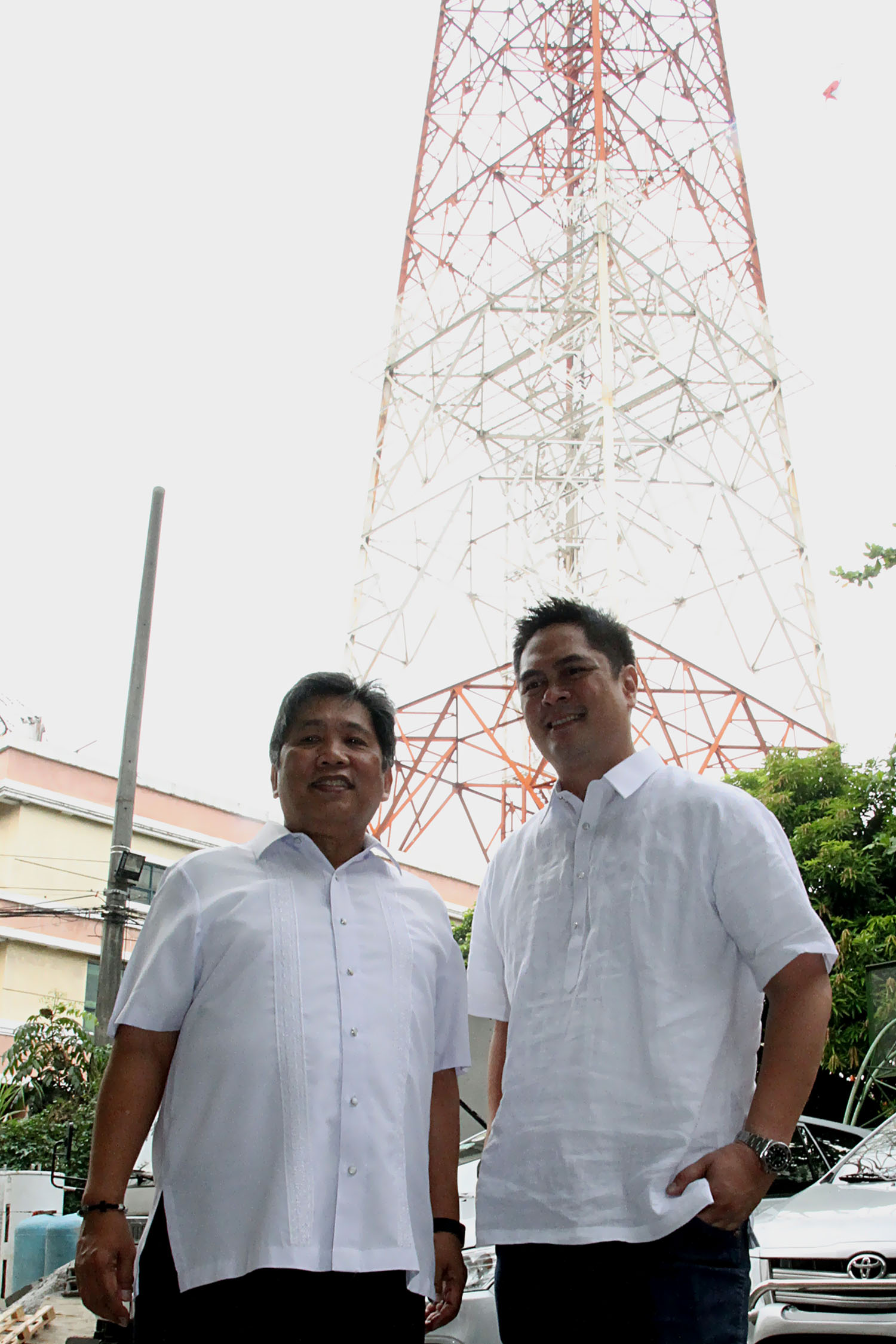 Incoming Presidential Communications Operations Office (PCOO) Secretary Martin Andanar (right) pose for a souvenir photo with outgoing Secretary Herminio Coloma Jr. during their visit at the different government media offices located at the National Media Center in Quezon City on Monday. Seen at the background is a portion of the 500-foot high PTV4 transmitter tower. (Photo: Oliver Marquez/PNA)