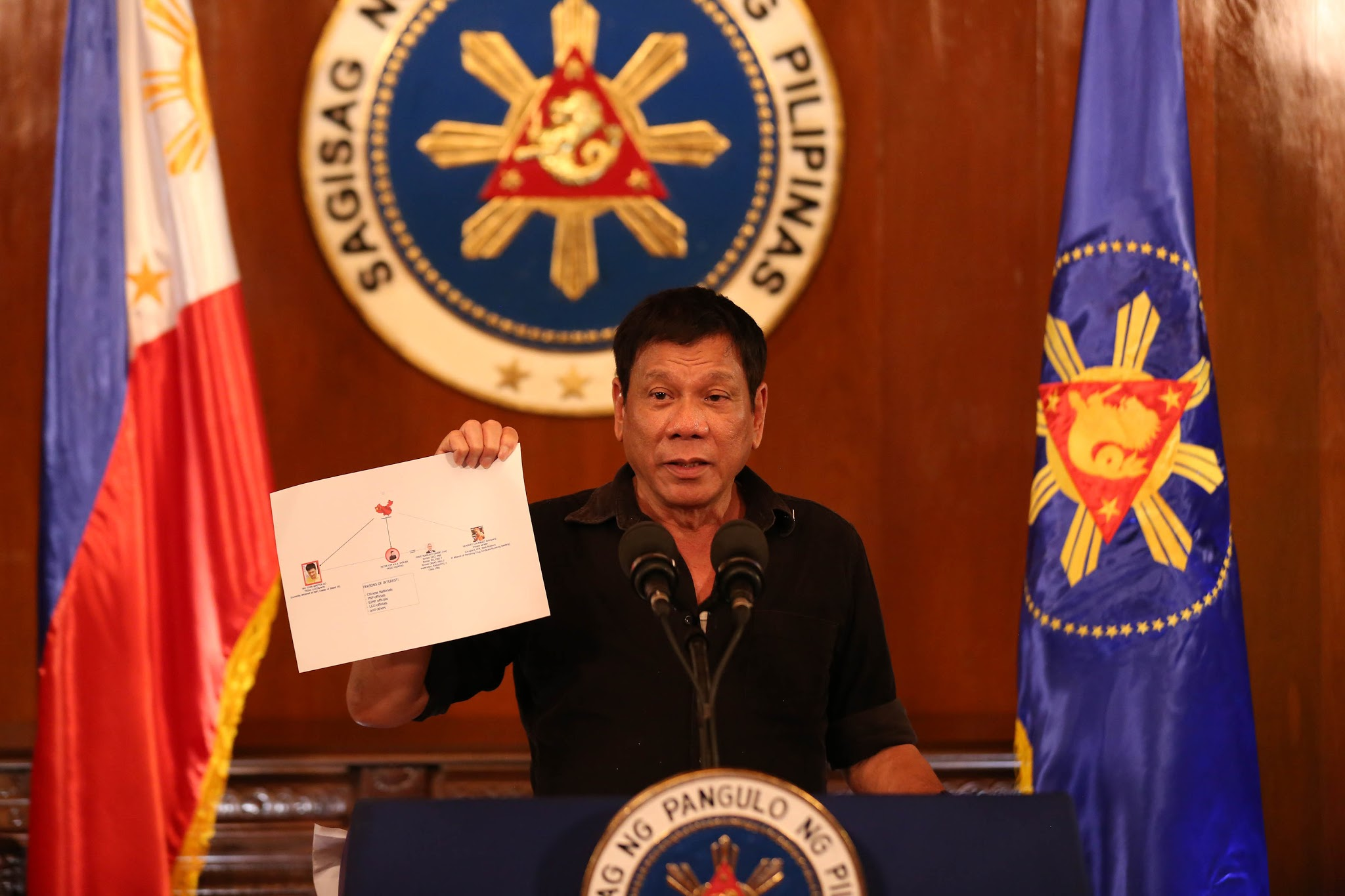 FILE PHOTO: President Rodrigo R. Duterte shows a copy of a diagram showing the connection of high level drug syndicates operating in the country during a press conference at Malacañang on July 7, 2016. (Photo by KING RODRIGUEZ/Presidential Photographers Division)