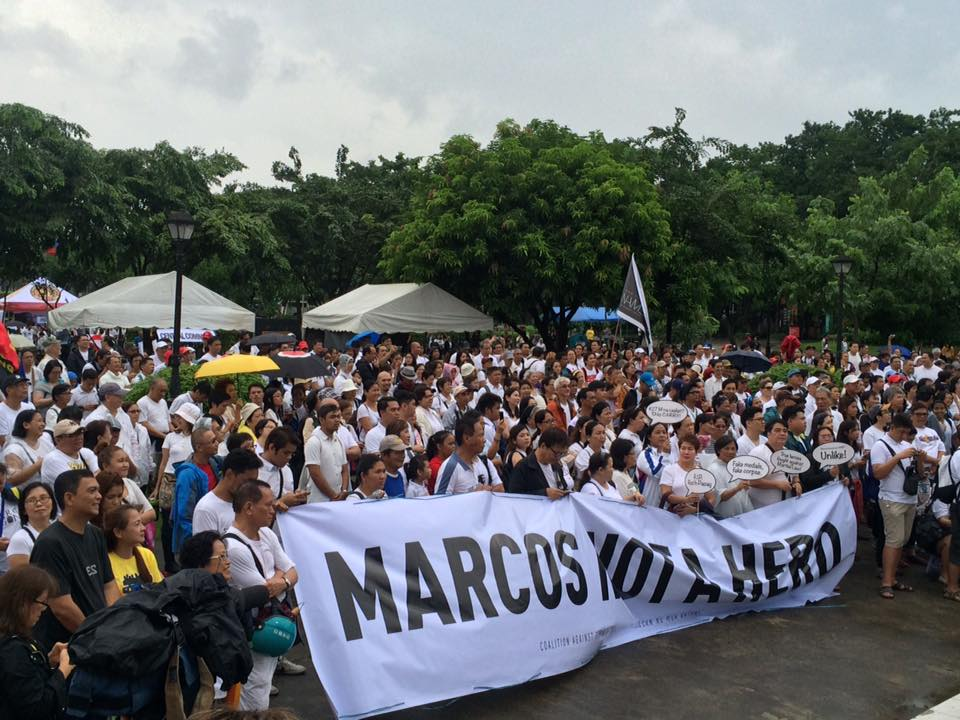 """MARCOS NOT A HERO: Protestors in Rizal Park, Sunday, hold up a banner that says, """"Marcos Not a Hero"""" in protest of a hero's burial for former president Ferdinand Marcos Sr.. (Photo by Akbayan Youth)"""