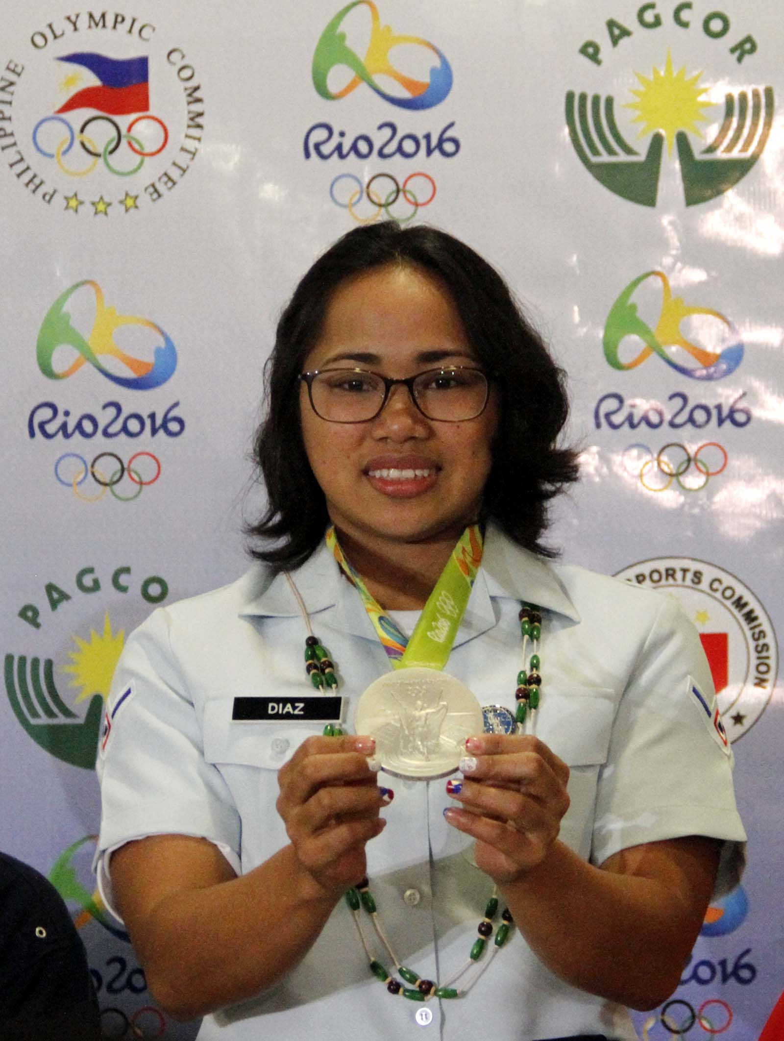 A beaming Olympian Silver Medalist Hidilyn Diaz displays her medal shortly upon her arrival at the Ninoy Aquino International Airport (NAIA) Terminal 3 in Pasay City from Rio de Janeiro, Brazil on Thursday afternoon. (PNA photo by Avito C. Dalan)