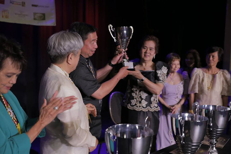 Rodel Rodis (Juror) hands Loving Cup to Feed the Hungry chair Celia Donahue. From left are Rozita Lee (Juror) and Michael Dadap (NaFFAA co-founder). Two ladies on right are unidentified members of Feed the Hungry. (Contributed photo)