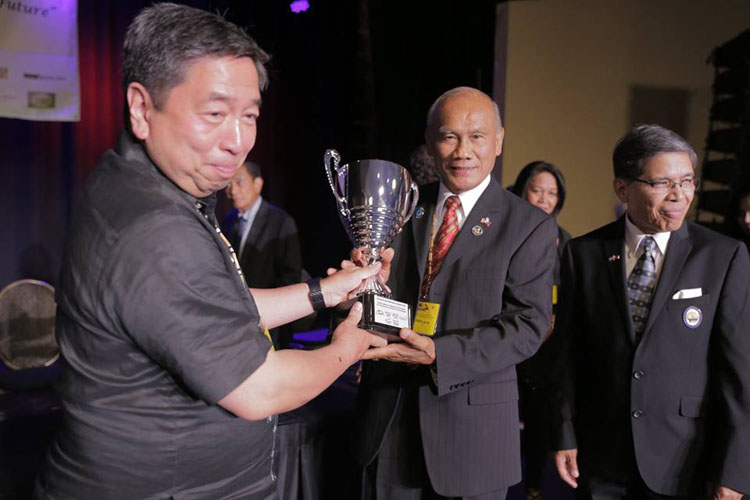 Rodel Rodis handing Loving Cup to Nony Abrajano, FilAmCAG Chairman. Beside him is unidentified FilAmCAG member. (Contributed photo)