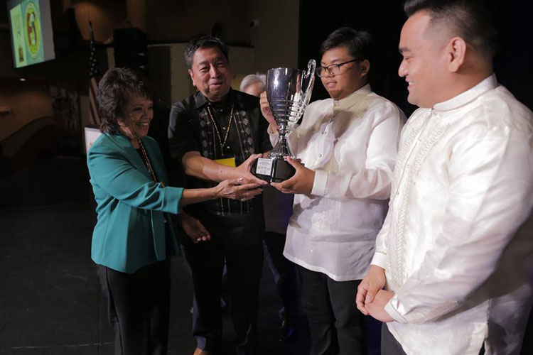 Rozita Lee and Rodel Rodis hand Loving Cup to officers of Filipino Cultural School. Holding cup is Matthew Menchavez and looking on (right) is Paolo Roca, FCS President. (Contributed photo)
