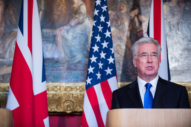 """Michael Fallon, a dependable lieutenant to Prime Minister Theresa May, quit as defence secretary late Wednesday, saying his past behaviour """"may have fallen below the high standards"""" expected. Fallon had apologized after a newspaper reported that he had repeatedly touched a journalist's knee at a function in 2002, and reports suggested more allegations about him might emerge. (Photo by DOD photo by U.S. Army Sgt. Amber I. Smith via Jim Mattis/Flickr, CC BY 2.0)"""
