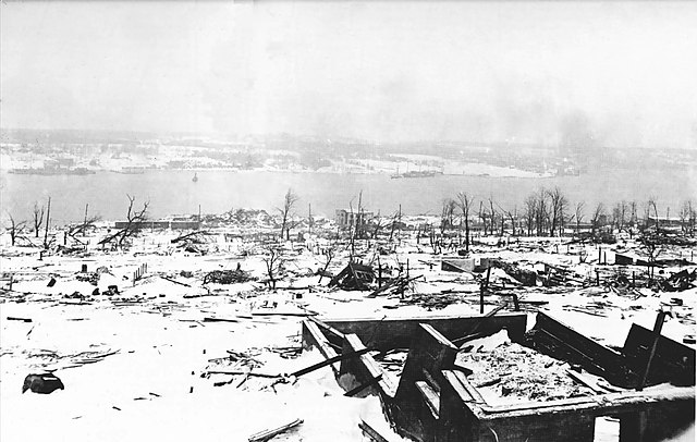 A view across the devastation of Halifax two days after the explosion, looking toward the Dartmouth side of the harbour. Imo is visible aground on the far side of the harbour. (Photo By Unknown - Derivative of File:DNDHfxExplosion-2.jpg. Nova Scotia Archives and Records Management, Negative Number DNDHfxExplosion-2, Public Domain)