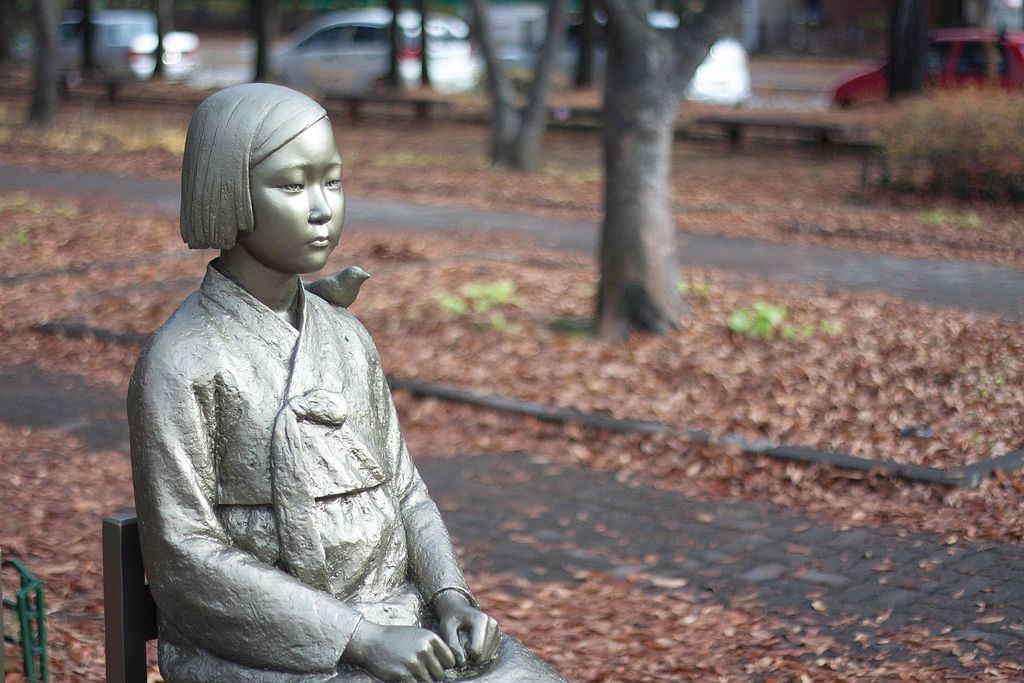 Statue of Peace. Sad looking Korean woman in traditional garb with clenched fists. Park-like background with tree trunks and leaves on ground. Autumn setting.(Photo By YunHo LEE - peace statue comfort woman statue (3), CC0)