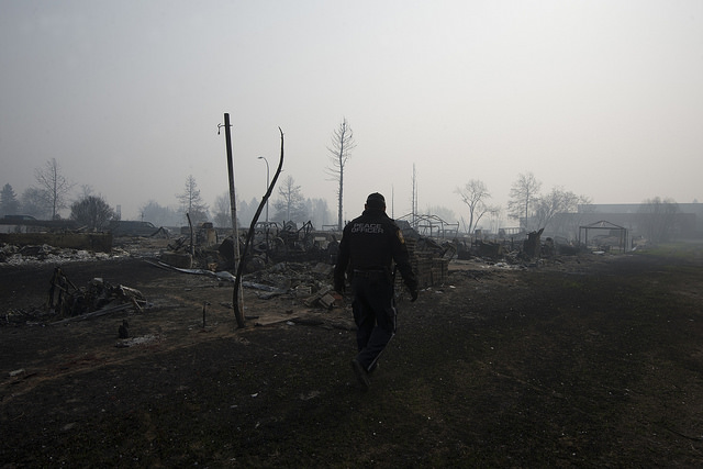 A Wood Buffalo peace officer walks through thick smoke in the Beacon Hills neighbourhood of Fort McMurray on Saturday, May 14, 2016. (File photo by Chris Schwarz/Government of Alberta via Premier of Alberta/Flickr, CC BY-ND 2.0)