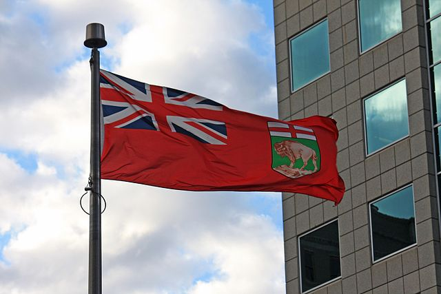 The flag of the Canadian province of Manitoba, flying in downtown Winnipeg (Photo By Makaristos - Own work, Public Domain)