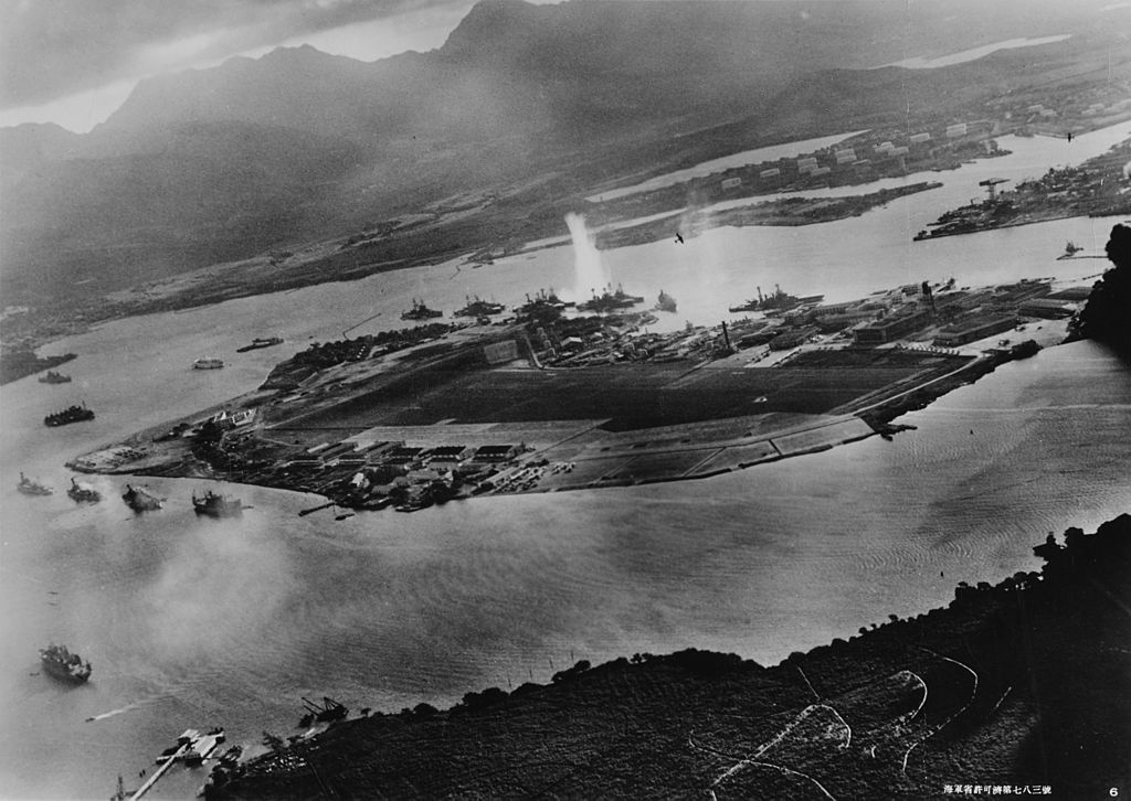 Photograph taken from a Japanese plane during the torpedo attack on ships moored on both sides of Ford Island shortly after the beginning of the Pearl Harbor attack.  (Photo By Unknown - Official U.S. Navy photograph NH 50930., Public Domain)