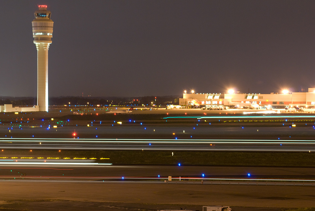 A view of the International Concourse E and Control Tower at night (Photo By Omoo at English Wikipedia, CC BY 3.0)