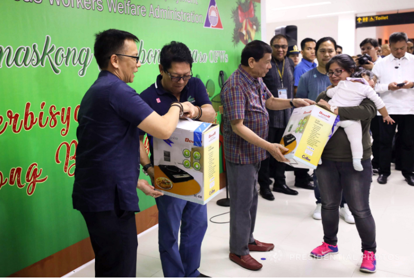 President Rodrigo Roa Duterte leads the distribution of appliances to the arriving overseas Filipino workers (OFWs) during the Pamaskong Salubong Para sa OFWs at the Clark International Airport in Pampanga on December 7, 2017. Also in the photo is Labor and Employment Secretary Silvestre Bello III. (Photo by Ace Morandante/Presidential Photo)