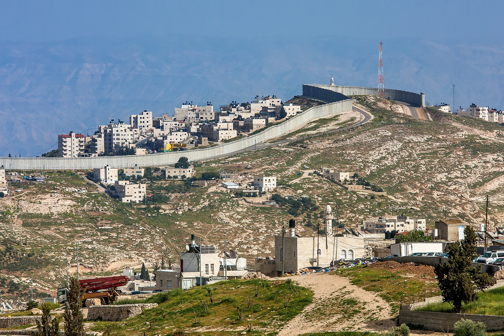 Palestinians shuttered schools and shops and called for protests in West Bank towns on Thursday, while the leader of the Hamas militant group called for a new armed uprising, in widespread show of anger over President Donald Trump's move to recognize Jerusalem as Israel's capital (Seen in this photo is a small village and Palestinian town on the hill behind separation wall on the West Bank in Israel).