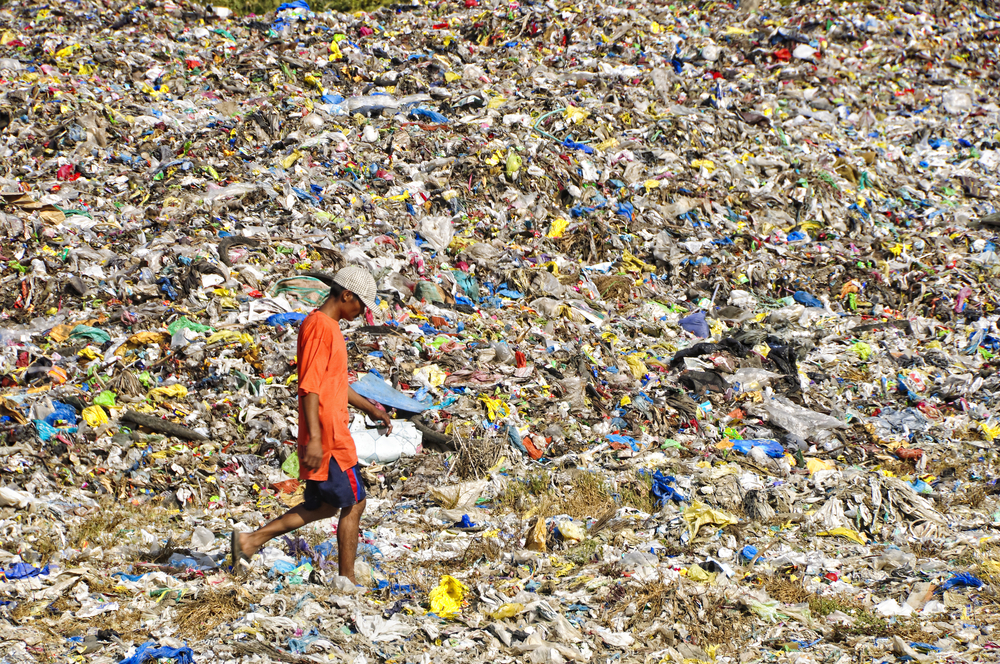 """""""I call on Prime Minister Justin Trudeau to be true to his word and take back the trash that was shipped to our country in violation of our laws. This can only enhance Canada's self-imposed burden of being a champion of human rights and the rule of law"""", Pimentel said. (Seen in this photo by Antonio V. Oquias / Shutterstock.com is an unidentified man crossing a sea of garbage on foot on February 12, 2010 in Cavite, Philippines)"""