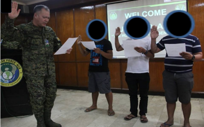TOWARDS A NEW BEGINNING. Three NPA rebels, Ka Jelly, Ka Kem, and Ka Dodong (their faces covered for security reason), who surrendered and took their oath of allegiance before Brig. Gen. Alan Arrojado, commanding general of the Joint Task Force of the Armed Forces of the Philippines (JFT/AFP) in Camp Aguinaldo last week, May 19.  (PNA photo)